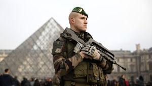 Soldat med maskingevär vaktar folkmassorna utanför konstmuseet Louvren i Paris.