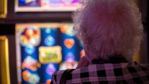 Anonyymi vanha nainen pelaa rahapeliä Casino Helsingissä.