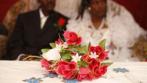 Brudpar vid ett bord med blombukett.