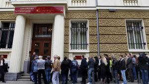 Folk står i kö utanför en bulgarisk bank i huvudstaden Sofia den 20 juni.