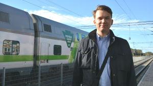 Jacob Storbjörk står på perrongen vid Bennäs tågstation i Pedersöre framför ett VR-tåg av modellen Intercity
