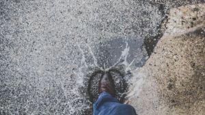 Regn och en fot i en vattenpöl.