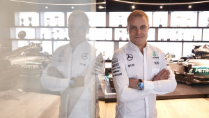 Vitklädde F1-föraren Valtteri Bottas poserar bredvid glasvägg.