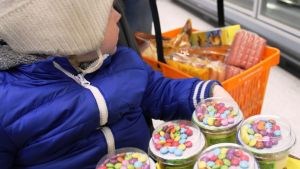 Lapsi vaunuissa karkkijogurtit sylissä.