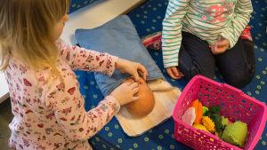 Dagisbarn leker med docka