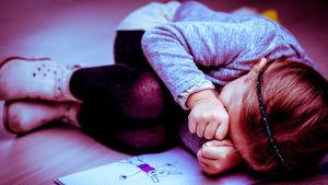 En liten flicka ligger och gråter.