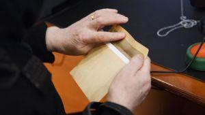 En äldre kvinnas händer klistrar igen ett valkuvert.