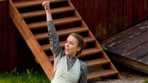 Alexandra Mangs som Alma, med knuten näve i vädret.