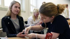 Anni Lundahl tar ett hemoglobinprov på Jonna Hiltunen.