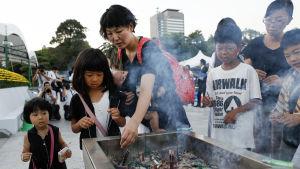 Hiroshimabor tände rökelse vid minnesmärket till offren, strax innan ceremonin inleddes på söndagen.