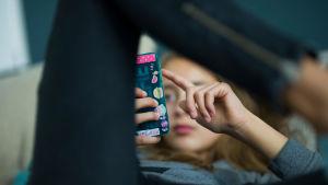 Tjej som ligger och tittar på sin telefon.