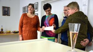 Fyra personer poserar med en check.
