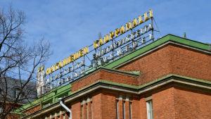 Fasaden av ett tegelrött hus med neonskylten Hagnäs saluhall