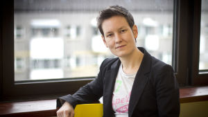 Porträtt av Anna Moring framför ett fönster klädd i kavaj och t-skjorta.