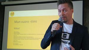 Ville Grönberg puhuu mikrofoniin, taustakankaalla Mun vuoro -tiimin esitys