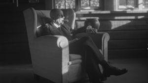 Säveltäjä Jean Sibelius istuu nojatuolissa ja polttaa sikaria Ainolassa.