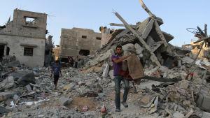 Palestinier bär ut sina ägodelar ur husruiner i norra Gaza på söndagen då eldupphöret pågått i tre dagar.