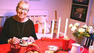Ruth Lawast sitter vid dukat julkaffebord.