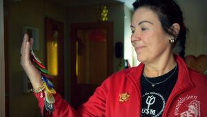 Sussi Gröndahl håller upp sina nyckelringar hon fått från NA, anonyma narkomaner.
