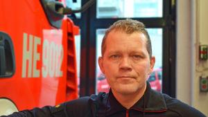 Brandmästare Vesa Berg invid en brandbil.