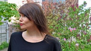 Författaren Hannele Mikaela Taivassalo poserar i Morgonöppets trädgård.