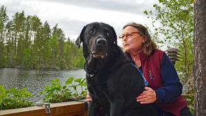 Arja Alho och assistenthunden Kalle blickar ut över sjon.