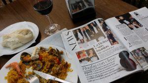Pöytä, jolla lautanen paellaa, espanjalainen naistenlehti ja lasi punaviiniä