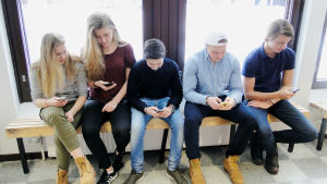 Ett gäng skolelever sitter på en bänk och surfar på sina smarttelefoner.
