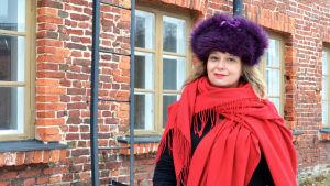 Kvinna i röd sjal och lila pälsmössa utanför rödtegelhus.