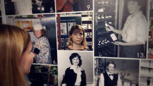 Maria Ollila har sammanställt utställningen om kvinnor i restaurangbranschen på Hotell- och restaurangmuseet. Här tittar hon in i en spegel som finns på en kollagevägg.