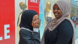 Två muslimska tonårsflickor i ett köpcentrum, skrattar.