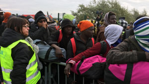 Hjälparbetare bistår då flyktinglägret Djungeln töms i Calais.
