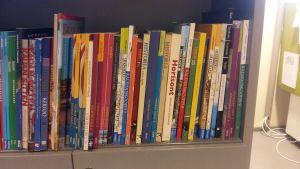 Skolböcker i rad i en hylla.