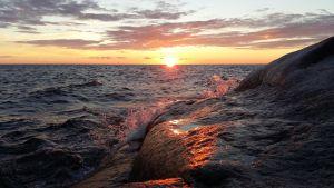 Vågor färgas rosa då de slår mot en klippa i solnedgången.