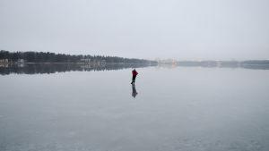 Skridskoåkare på grå blank is utanför munksnäs, kägeluddens skyskrapor skymtar i morgondiset