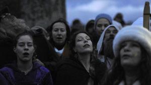 Kvinnor som firar vintersolståndet vid Stonehenge i England. Deras ögon är slutna.