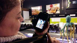 En bloggare visar sin kamera med det foto hon tagit av en bläckfisk i tyg vid fiskdisken i Åbo saluhall.