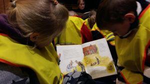 Anna-Katariina Suominen och Aaron Kantola med en Pettson-bok under sagostunden i Åbo huvudbibliotek.