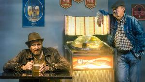 Tvä män i en bar med en jukebox mellan sig