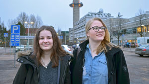 Helmi Nurkkala tittar in i kameran, Ida Salo tittar ut ur bilden, då de poserar på en parkeringsplats med Yletornet i bakgrunden.