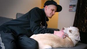 Alex Granqvist ligger i sin soffa och krafsar sin hund.
