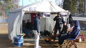 Asylsökande sitter vid en brasa utanför ett tält i Kristinestad.