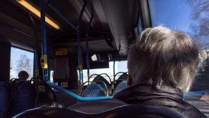 Eläkeläinen bussissa.