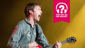James Blunt spelar gitarr och gapar med munnen.