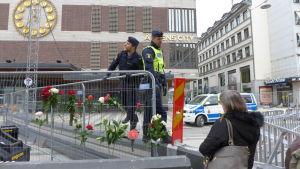 Folk sticker in blommor i stängslet vid varuhuset Åhléns.