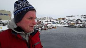 Jakob i röd jacka, i profil, blickar ut mot havet, en oljebehållare och små hus i bakgrunden.