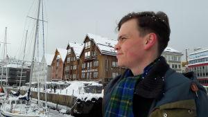 Anton blickar ut mot havet, segelbåtar, höghus i trä i bakgrunden.