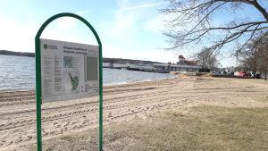 En skylt vid en strand där det står Knipans badstrand. Till höger syns ett träd och bakom det några byggnader.