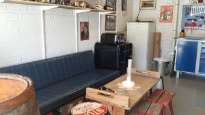 En blå lädersoffa bjuder in gäster till Sture Nylunds garage