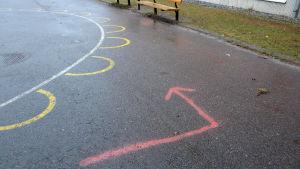 en pil har målats på skolgården för att barnen ska kunna springa maraton